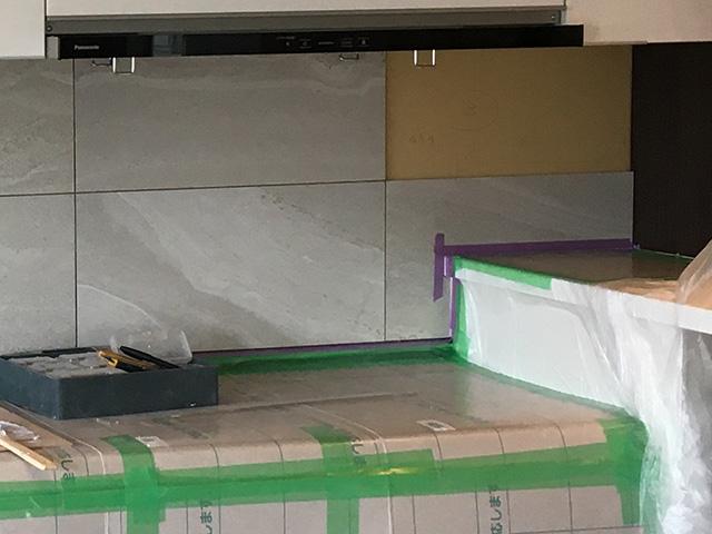 キッチン前の壁にタイルを貼っている施工途中の写真